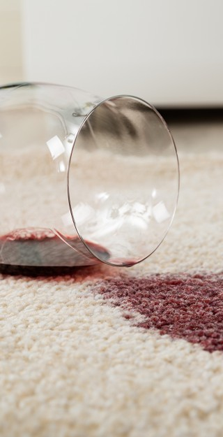 Red wine spilled from glass on carpet