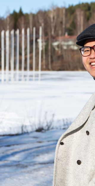 Young man outside in wintery scenery, smiling.