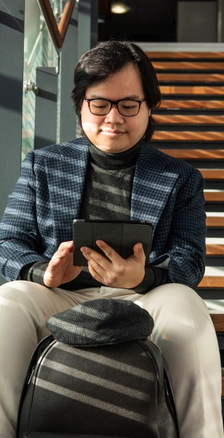 Young man sitting on the stairs, looking at the tablet device in his hands.
