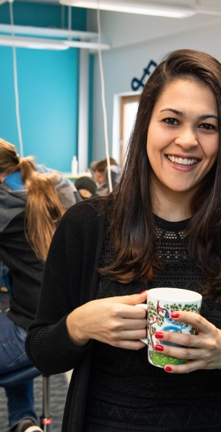 Young woman looking at the camera smiling and holding a coffee cup, young men working with their laptops in the background.